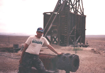 Gary leans on the remains of an air compressor quartz mountain mine
